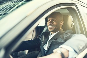 African businessman smiling while driving his car in the city