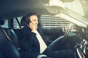 Smiling businessman talking on a phone in his car