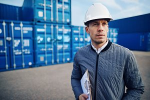 Dock manager standing alone in a commercial shipping yard