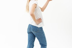 Lifestyle Concept: Portrait woman pointing or pushing something with index finger. Beautiful casual young woman isolated on white background in full length standing in profile.