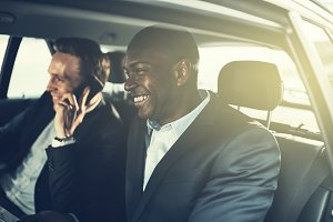Smiling African businessman and colleague being driven to work