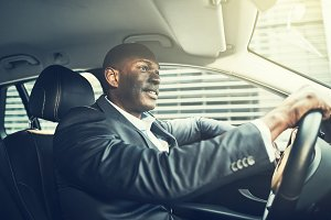 Smiling African businessman driving through the city in a car