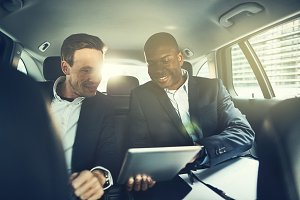 Smiling businessmen using a tablet while driving in the city