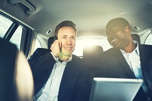 Smiling businessmen working together while driving in the city
