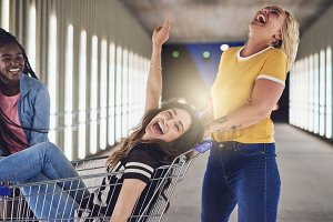 Carefree young girlfriends playing with a shopping cart at night