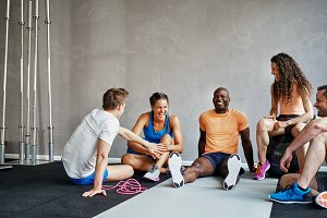 Smiling friends in sportswear sitting together in a gym