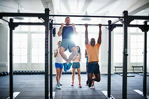 People encouraging two men doing pullups in a health club