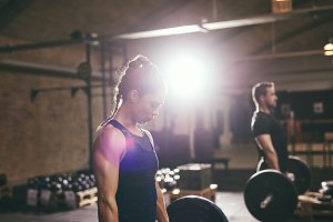 Sporty people doing workout with heavy barbells