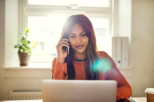 Smiling female entrepreneur talking on a phone and working online