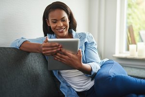 Young African woman sitting at home using a digital tablet