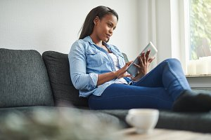 Young African woman sitting on her couch using a tablet
