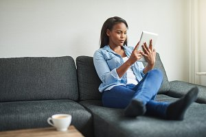 Young African woman relaxing on her sofa with a tablet