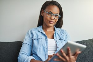 Confident African woman sitting on her sofa with a tablet