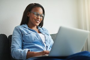 Smiling young African woman sitting at home working online