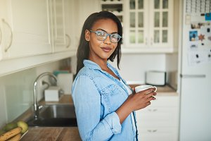 Smiling young African woman standing in her kitchen drinking coffee