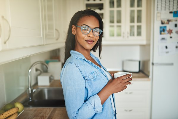 People Stock Photos: Stefan & Janni - Smiling young African woman standing in her kitchen drinking coffee