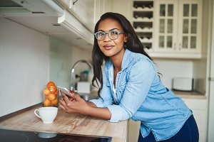 Smiling African woman leaning on her kitchen counter sending texts