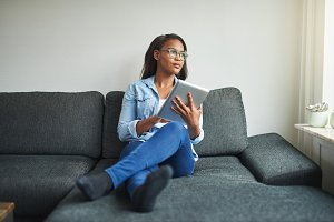 Young African woman relaxing on her sofa browsing the internet