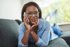 Smiling African woman relaxing at home talking on a cellphone