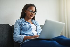Young African woman relaxing at home using a laptop
