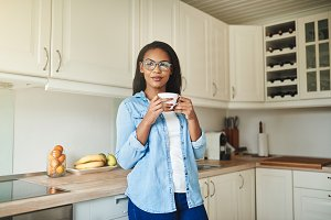 Smiling African woman leaning on her kitchen counter drinking coffee