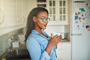 Young African woman standing in her kitchen with a coffee