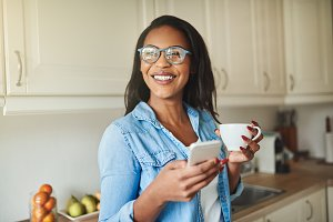 Laughing young African woman drinking coffee and reading text messages