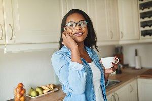Young African woman drinking coffee and talking on a cellphone