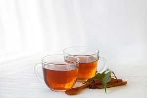 Glass cup of black tea with cinnamon