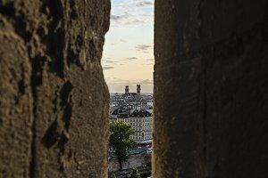 Narrow window in stone wall in Paris