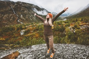 Happy woman traveler raised hands