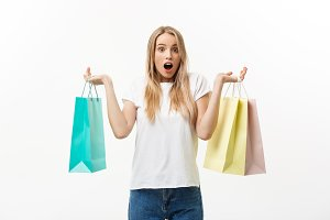 Lifestyle Concept: Portrait shocked young brunette woman in white summer shirt posing with shopping bags isolated over white background.