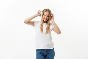 Lifestyle Concept: Portrait of a cheerful happy girl student listening to music with headphones while dancing isolated over white background