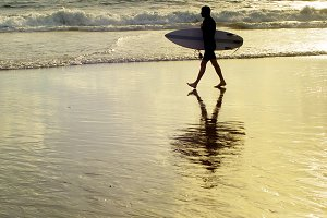 Surfer with surfboard walk beach