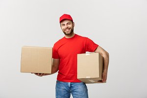 Delivery Concept: Smiling handsome caucasian delivery man holding a paper box. Isolated over grey background.
