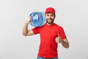 Portrait smiling bottled water delivery courier in red t-shirt and cap carrying tank of fresh drink and showing thumb up isolated over white background