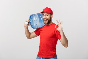 Portrait smiling bottled water delivery courier in red t-shirt and cap carrying tank of fresh drink and showing ok isolated over white background.