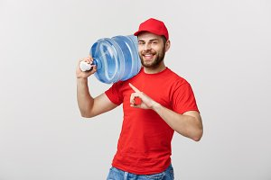 Portrait smiling bottled water delivery courier in red t-shirt and cap carrying tank of fresh drink and pointing finger isolated over white background.