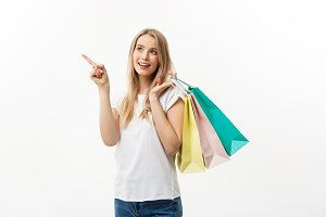 Shopping and Lifestyle Concept: Young cheerful woman holding colorful shopping bag and pointing finger. Isolated over white background.