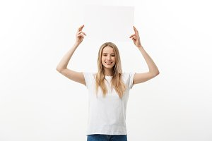 Blank sign. Woman holding empty blank white sign above her head. Excited and happy beautiful young woman isolated on white background.