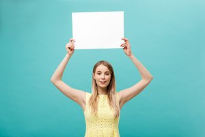 Portrait beautiful young caucasian woman holding a blank paper isolated on pastel blue background