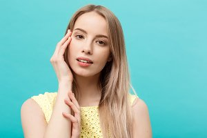 Beautiful Woman Face Portrait Beauty Skin Care Concept: beauty young caucasian female model girl touching her face skin cheeks hands fingers. Fashion Beauty Model isolated on blue.