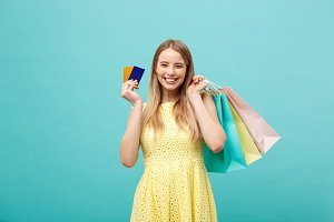 Shopping and Lifestyle Concept: Beautiful young girl with credit card and colorful shopping bags. Isolated on blue background
