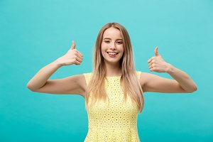Success and Lifestyle Concept: Young happy cheerful woman showing thumb up over pastel blue background.