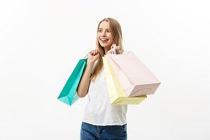 Shopping and Lifestyle Concept: Young happy summer shopping woman smiling and holding shopping bags isolated on white background