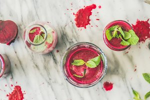 Fresh morning beetroot smoothie or juice in glasses, marble background