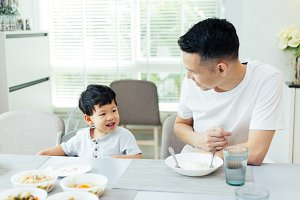 Happy Asian family of father and son playing and laughing while having dinner