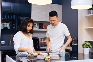Young Asian couple cooking together while woman is feeding food to man at the kitchen. Happy couple and relationship concept