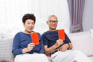 Chinese Asian senior elders giving red envelope or Hong bao to younger generation during Chinese new year