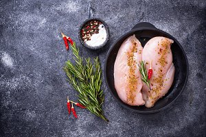 Raw chicken fillet in cast iron pan